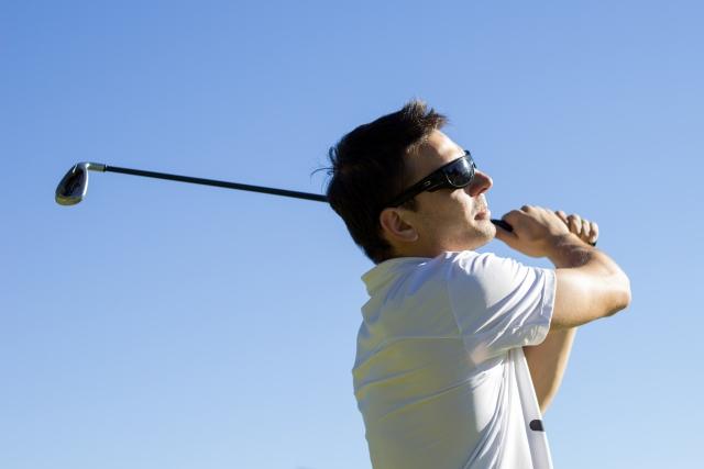 ゴルフを打つ男性